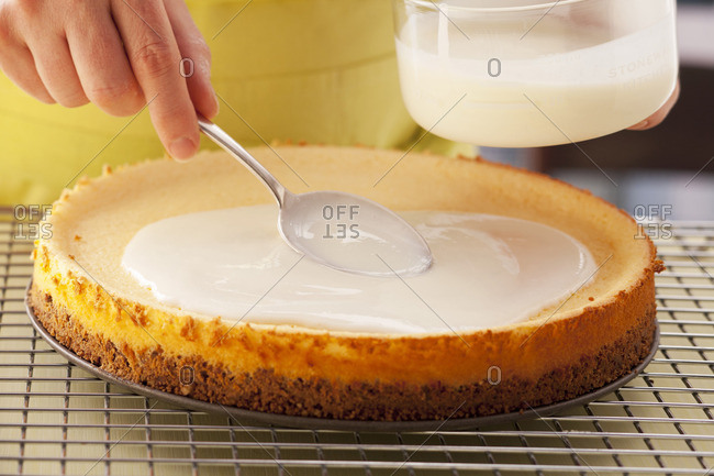 Spreading California cheesecake with sour cream icing