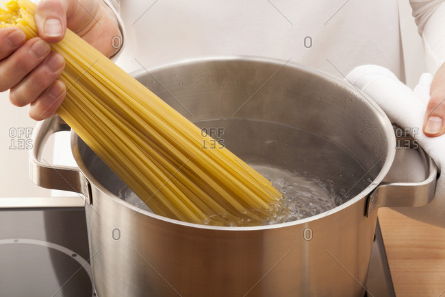 Putting spaghetti into boiling water