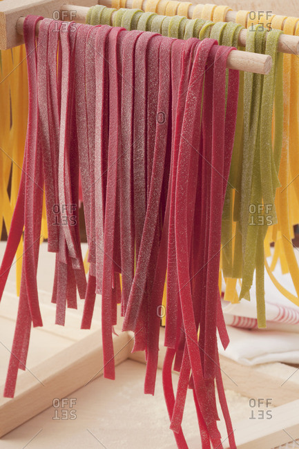 Colorful tagliatelle hanging to dry