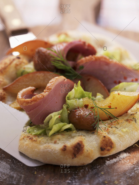 Tart flambe topped with goose breast, chestnuts, white cabbage and sliced pears