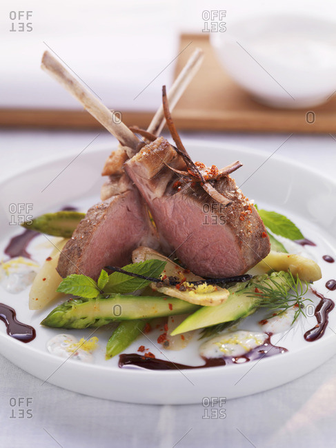 Medium rare saddle of lamb on a bed of asparagus