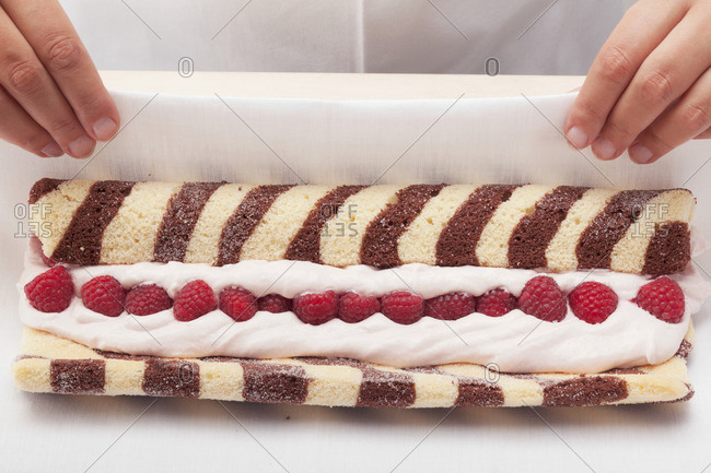 Black and white sponge roll with a raspberry filling being made