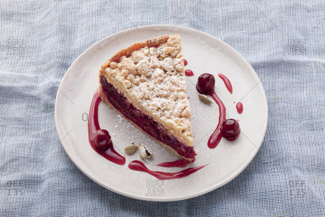 A slice of cherry crumble cake with cardamom pods