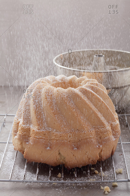 A ring cake being dusted with icing sugar