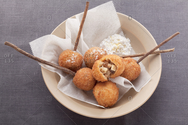 Deep fried dough balls with a sweet filling in a beige dish