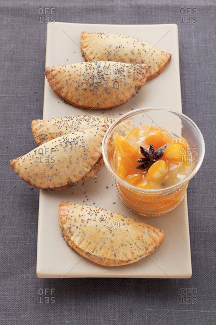 Sweet poppy seed pierogi (steamed dough parcels) with orange dip on an oblong plate