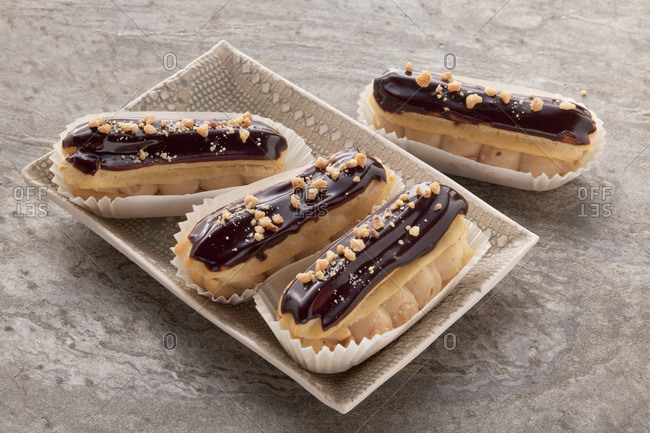 �clairs with a chocolate glaze in a small oblong dish on a grey surface