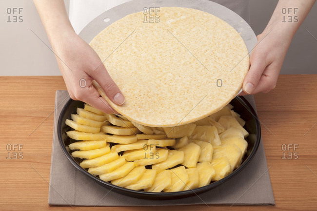 Hands laying the cake base onto pineapples in a baking tin