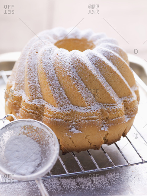 A Bundt cake with icing sugar on a wire rack