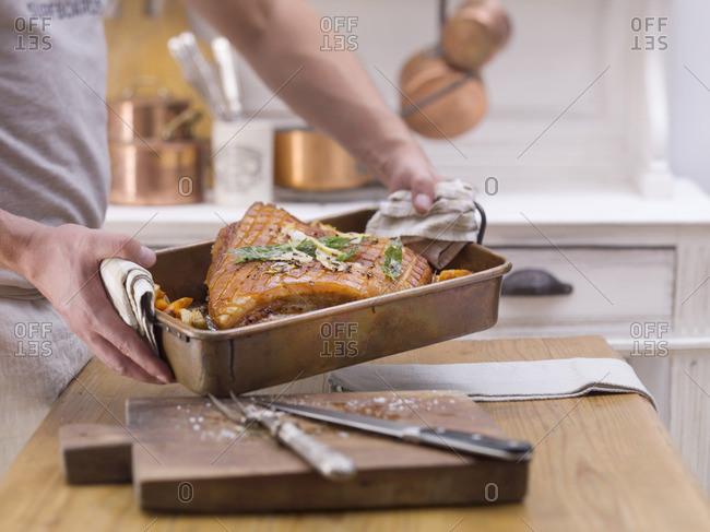 A man holding crispy roast pork in a roasting tin