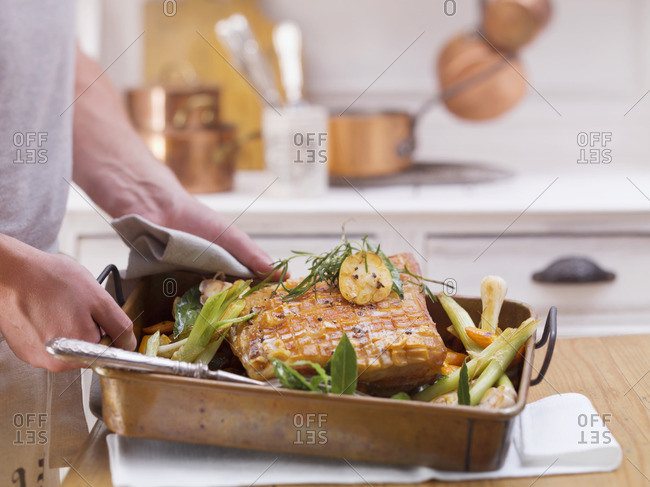 Roast pork with vegetables in a roasting tin