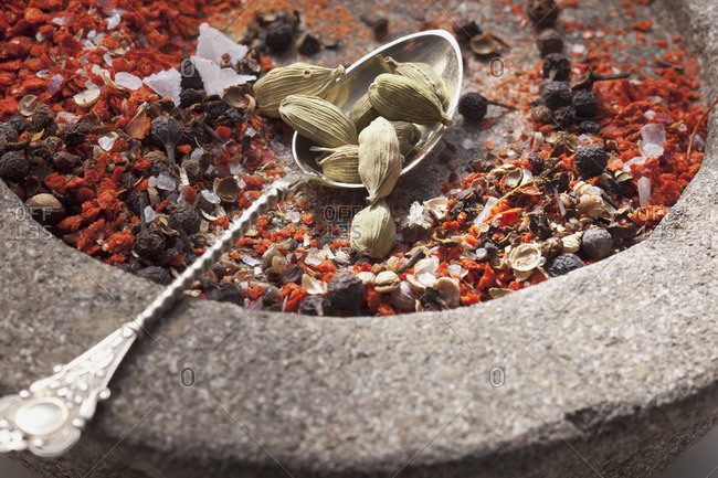 Spices for a spice mixture in a stone mortar and on a spoon
