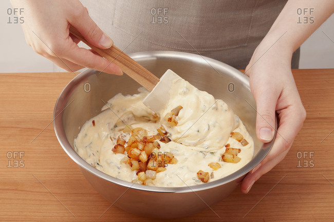 Cream cheese being mixed with pineapple and potato pieces