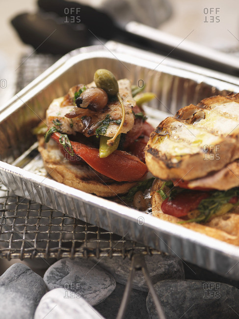 Barbecued chicken and vegetable sandwiches in an aluminum tray