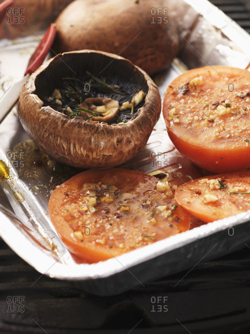 Barbecued Portobello mushrooms and tomatoes in an aluminum tray