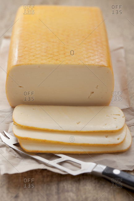 cheese, butter (mild, semi-soft cheese), partly sliced, on paper with a cheese knife