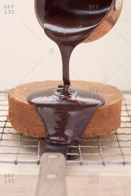 Chocolate cake (rich chocolate cake from Austria) being coated with chocolate glaze