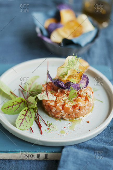 Salmon tartar with fresh herbs and colorful potato chips