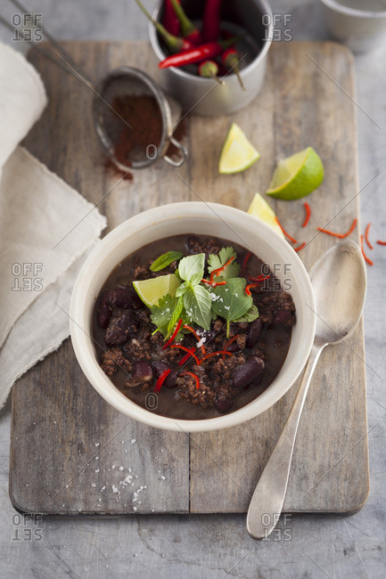 Chili con carne with herbs on a wooden board