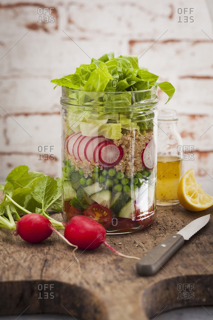 A layered salad with peas, radishes, cucumber and tomatoes in a jab