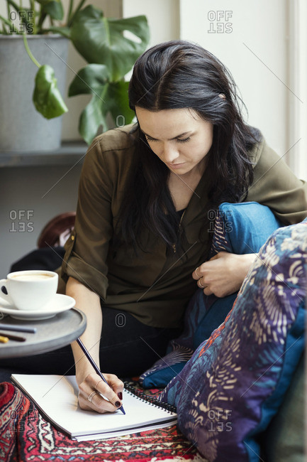 Concentrated female blogger writing in spiral notebook while sitting on sofa