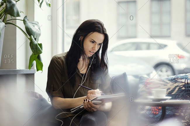 Creative businesswoman wearing headphones while writing in spiral notebook at office