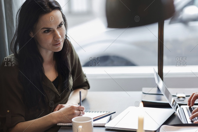 Businesswoman with spiral notebook while sitting at table in modern office
