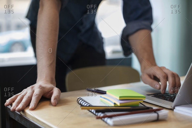 Midsection of businessman working on laptop at table in creative office