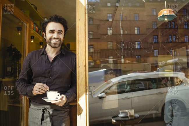 Portrait of happy barista holding coffee cup while standing at doorway