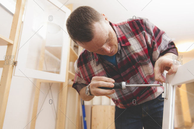 Mature man using screwdriver on cabinet door at home