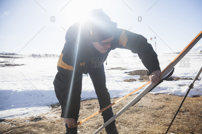 Mature man in warm clothing applying grip tape on ski at snow covered landscape