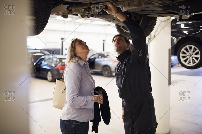 Male expert with client standing under car at repair shop