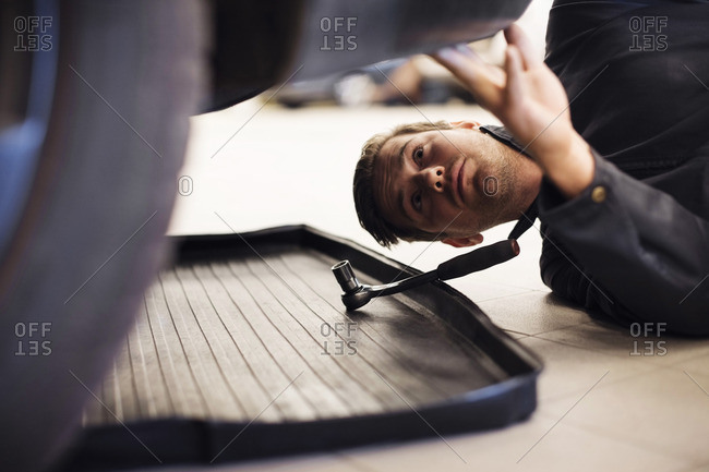 Close-up of technician repairing car while lying down in shop
