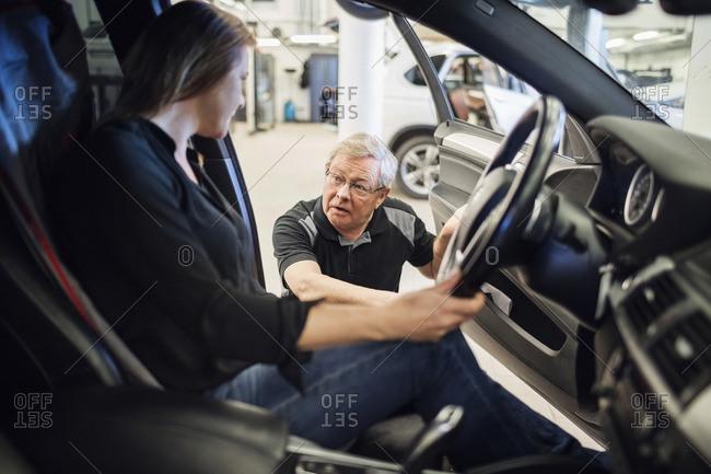 Senior expert discussing with female customer sitting in car at repair shop