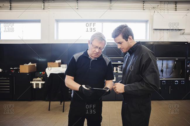 Senior mechanic and expert using digital tablet at auto repair shop