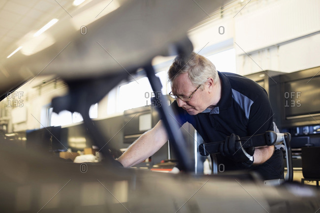 Senior mechanic holding technology while examining car