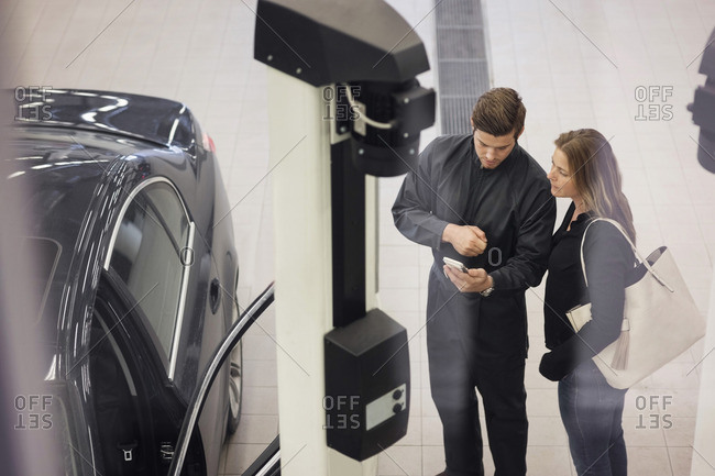 High angle view of mechanic and female customer using mobile app seen through glass