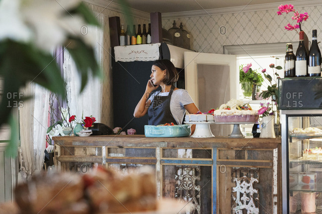 Serious woman talking on phone while standing by counter at cafe