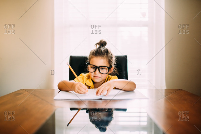Girl with glasses writing