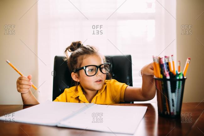 Studious girl picking a pencil