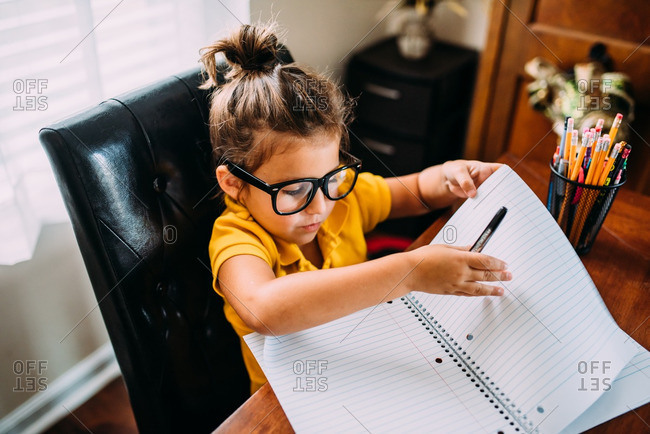 Girl with glasses writing in notebook