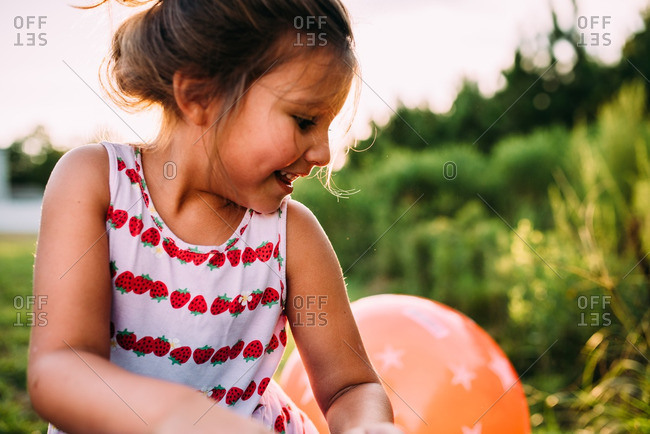 Girl in yard by bouncy ball