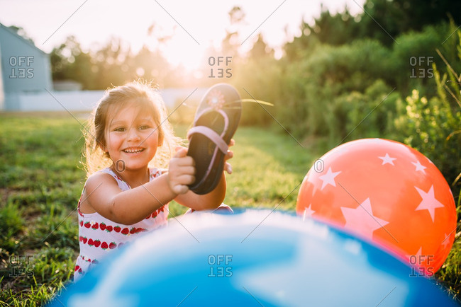 Girl holding shoe by bouncy balls