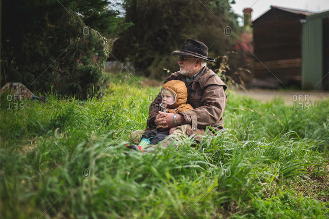 Grandfather sitting with grandson in grass at a farm