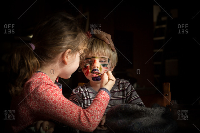 Girl painting toddler boy's face