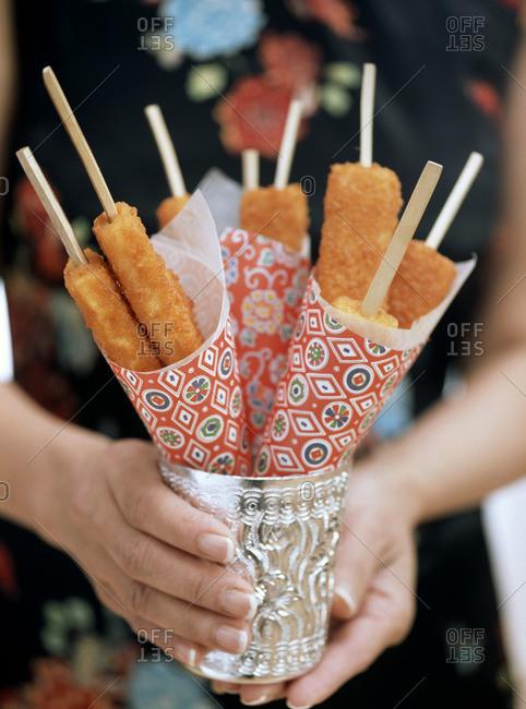 Woman holding fish finger kebabs in mug