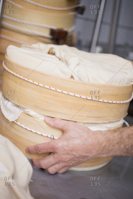Hand holding wrapped cheeses in round wooden molds
