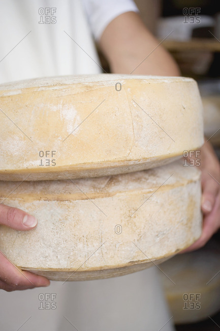 Person holding two large cheeses (, Alpine cheese)