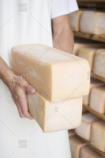 Man holding two blocks of cheese in a cheese dairy