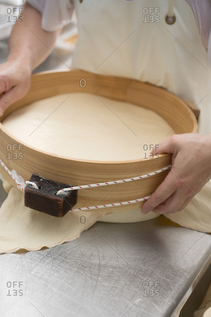 Cheese dairy worker holding round cheese in wooden mold